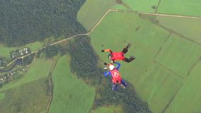 Skydiving. On a sunny summer day, parachutist athletes show performances in the sky stock video