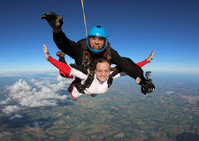Skydiving tandem jump cheerful. On a winter day , the colors are wonderful. Instructor man, women student, have fun in the skies of Brazil Royalty Free Stock Photo