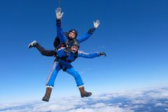 Tandem skydiving. Two guys are in the blue sky. stock photos