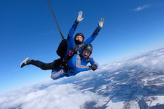 Tandem skydiving. Two guys are in the blue sky. royalty free stock images