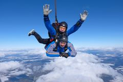 Tandem skydiving. Two guys are in the blue sky. stock images