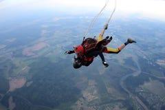 skydiving Tandemt hopp Mannen och den unga kvinnan faller i himlen tillsammans royaltyfria bilder