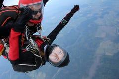 skydiving Tandemt hopp Mannen och den unga kvinnan faller i himlen tillsammans arkivbilder