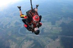 skydiving Tandemt hopp Mannen och den unga kvinnan faller i himlen tillsammans arkivfoton