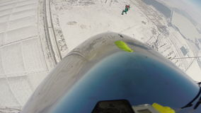 Skydiving video. Two skydivers perform a flight under a parachute during the winter stock video