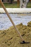 Skyffel för gammal hand som klibbas in i en hög av sand på en konstruktionsplats royaltyfria foton