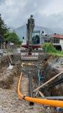 Skyffelgrävskopa som gräver gas- och maktrör Arkivbild