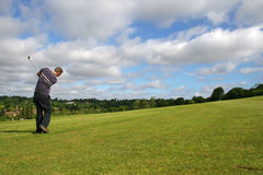 Skying it. A junior golf champion lofts the ball Royalty Free Stock Images