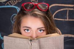 Skyldiga ögon av det unga studentflickanederlaget bak en bok Arkivbilder