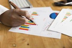 Skyler över brister den hållande pennan för affärsmanhanden med graf- och diagramanalys Arkivbilder