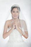 Skyler den härliga asiatiska kvinnan för ståenden i den vita bröllopsklänningen med Royaltyfri Fotografi