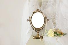 Skyler den ovala spegeln för gammal tappning och den härliga vita bröllopsklänningen och på stol Royaltyfri Foto