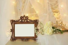 Skyler den ovala spegeln för gammal tappning och den härliga vita bröllopsklänningen och på stol med guld- girlandljus Fotografering för Bildbyråer