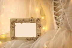 Skyler den ovala spegeln för gammal tappning och den härliga vita bröllopsklänningen och på stol med guld- girlandljus Royaltyfria Bilder