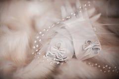 Skyler vita handskar för bröllopbruden med en pilbåge på varje finger på päls med pärlor och, morgonen av bruden, brölloptillbehö Royaltyfri Fotografi