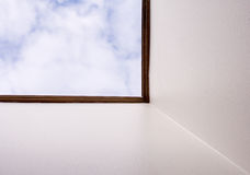 Skylight. View at blue and white sky through a skylight from inside the house Stock Photography