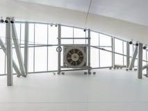 Skylight Fan. Ventilation fan installed near skylight on cross beams. Lights and steel framing members visible nearby Stock Photos