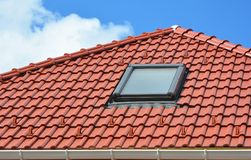 Skylight on red ceramic roof tiles house roof. Modern Roof Skylight. Attic Skylights Home Design. Roofing Construction. Clay Roof Tiles, Clay Tiles, Clay royalty free stock images
