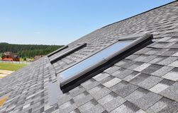 Skylights windows on modern house roof top.  Attic skylight windows on asphalt shingles roof. Outdoors royalty free stock photo