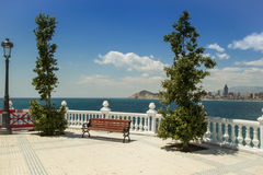 The skyline of Benidorm. Bench on balustrade and skyscrapers. Royalty Free Stock Image