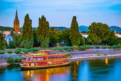 Skyline of Bonn, Germany. Beautiful night shot of great german city. Panorama with boat, trees, and historic architecture reflected in the water Royalty Free Stock Photography