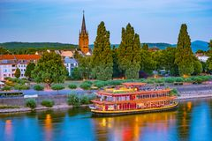 Skyline of Bonn, Germany. Beautiful night shot of great german city. Panorama with boat, trees, and historic architecture reflected in the water Royalty Free Stock Images