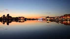 Skyline with the bright evening lights of Victoria City and sunset rays. lights form a mirror image on the water of the bay stock photo
