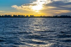 Skyline of Buenos Aires from the river at sunset. Skyline of Buenos Aires from the river Plate at sunset. The sky is behind the clouds and reflects in the water stock photo