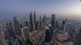 Skyline of the buildings of Sheikh Zayed Road and DIFC aerial night to day timelapse in Dubai, UAE. Skyline of the buildings near Sheikh Zayed Road and DIFC stock video footage