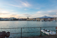 Skyline of Catania and its harbor with snowy volcano Etna Stock Photography
