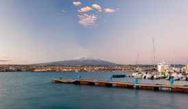 Skyline of Catania and its harbor with snowy volcano Etna in background after the sunset Stock Photography