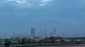 Skyline of construction cranes tower with skyscrapers on background in the Middle East day to night timelapse, Dubai. Skyline of construction cranes tower with stock video footage