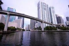 Skyline da cidade de Brickell e de Miami do centro com a ponte do trilho do motor do metro sobre o rio foto de stock