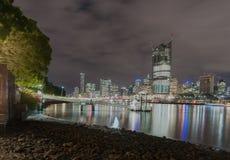 A skyline da cidade de Brisbane ilumina-se através do rio na noite dos vagabundos sul Foto de Stock Royalty Free