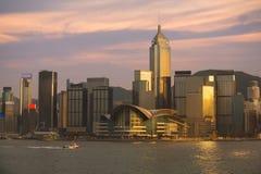 Skyline da cidade de Hong Kong na noite sobre o porto de Victoria com céu desobstruído e os arranha-céus urbanos Fotos de Stock Royalty Free
