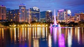 Skyline da cidade de Orlando, Florida no lago Eola no blurr dos logotipos da noite Imagens de Stock