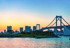 A skyline da cidade e a ponte do arco-íris através do Tóquio latem no por do sol Odaiba, Tokyo Imagens de Stock