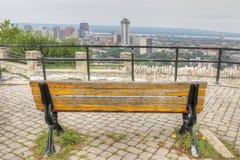 Skyline de Hamilton, Canadá com o banco de parque no primeiro plano fotografia de stock