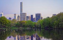 A skyline de Manhattan do Midtown refletiu da água do Central Park foto de stock