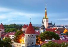 Skyline de Tallinn com kirik no por do sol, Estônia de Oleviste da igreja do St Olav foto de stock