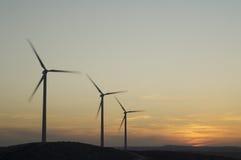 Skyline de três aerogenerators das energias eólicas no crepúsculo imagens de stock royalty free