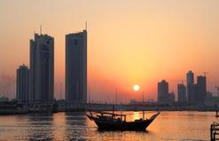 Skyline do Dhow e do Seef durante o por do sol em Barém Foto de Stock Royalty Free