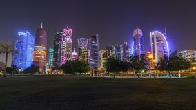 The skyline of Doha by night with starry sky seen from Park timelapse hyperlapse, Qatar. Trees on foreground. Illuminated skyscrapers and towers stock video footage
