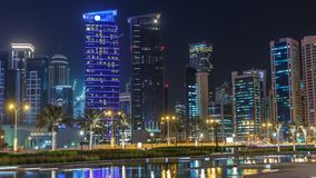 The skyline of Doha by night with starry sky seen from Park timelapse, Qatar. Illuminated skyscrapers and towers reflected in water of fountain stock footage