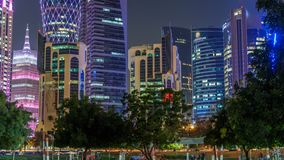 The skyline of Doha by night with starry sky seen from Park timelapse, Qatar. Trees on foreground. Illuminated skyscrapers and towers stock footage