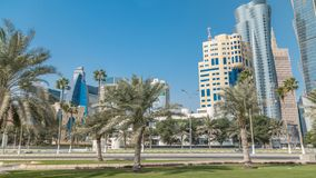 The skyline of Doha seen from Park timelapse, Qatar. Trees and palms on foreground. Mordern skyscrapers and towers on background. Traffic on road stock video