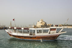 Skyline of Doha with traditional arabic dhows Stock Photography