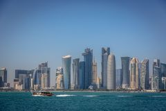 The skyline of Doha with a traditional boat in the foreground in Qatar, on a blue sky day, winter time, seen from the MIA Park. Qatar stock image