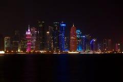 Skyline dos arranha-céus ocidentais da baía, na noite do Corniche Doha, Qatar Fotos de Stock Royalty Free
