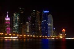 Skyline dos arranha-céus ocidentais da baía, na noite do Corniche Doha, Qatar Fotografia de Stock Royalty Free